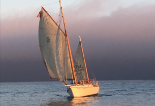 Classic-wood-yacht-under-sail-at-sunset